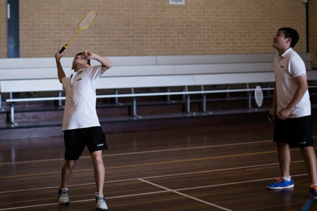 Students playing badminton in gym room